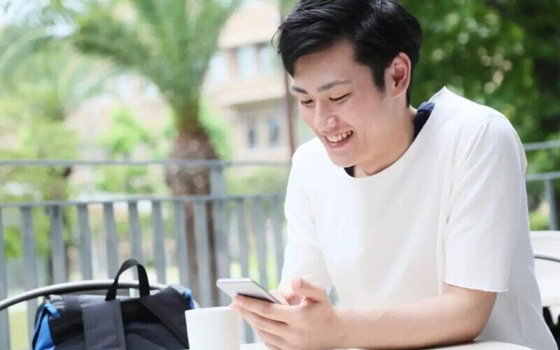 携帯で遊ぶ男